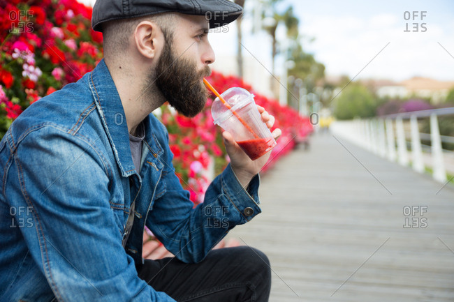 Handsome man drinking a smoothie with a straw and looking away. Horizontal outdoors shot.
