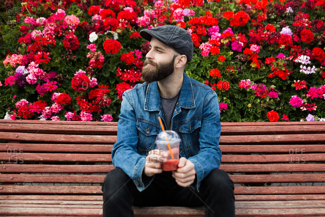 Handsome bearded man sitting on a bench with the fresh drink. Horizontal outdoors shot.