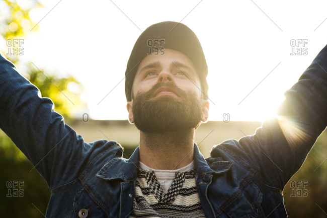 Young man in cap and denim jacket holding hands up and enjoying life looking happy.