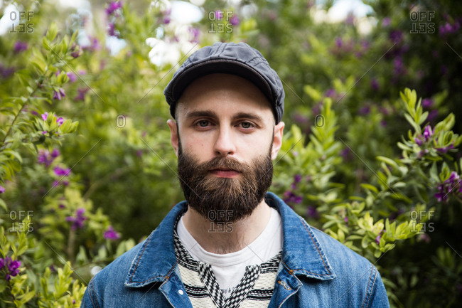 Young bearded man wearing cap and denim jacket looking unemotionally at camera in park.