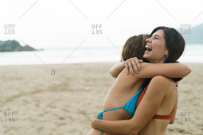 Side view of two laughing girls embracing on background of tropical beach.