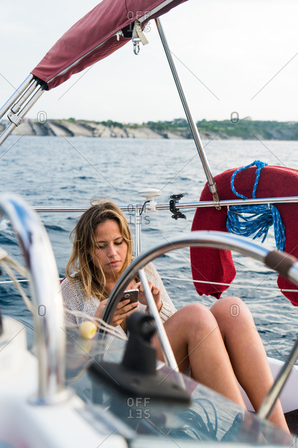 Girl with smartphone on sailboat