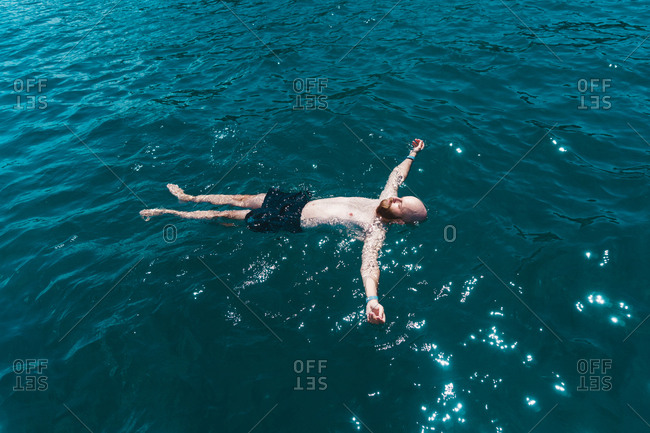 Bearded man in swimming shorts floating on surface of blue ocean water and relaxing in sunlight.