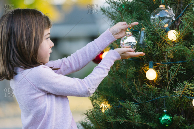 Little Adorable Girl decorating Christmas Tree