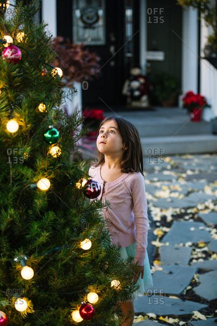 Little Adorable Girl decorating Christmas Tree