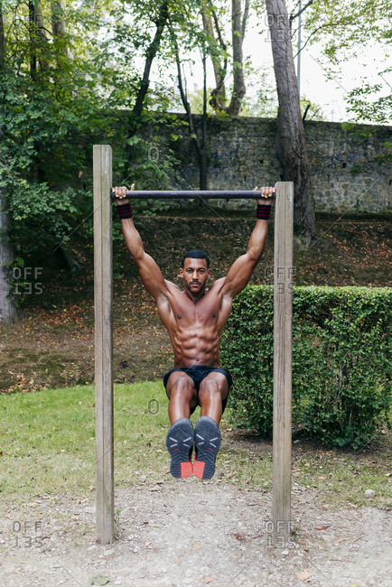 Athletic muscular black man hanging on bar during the workout.