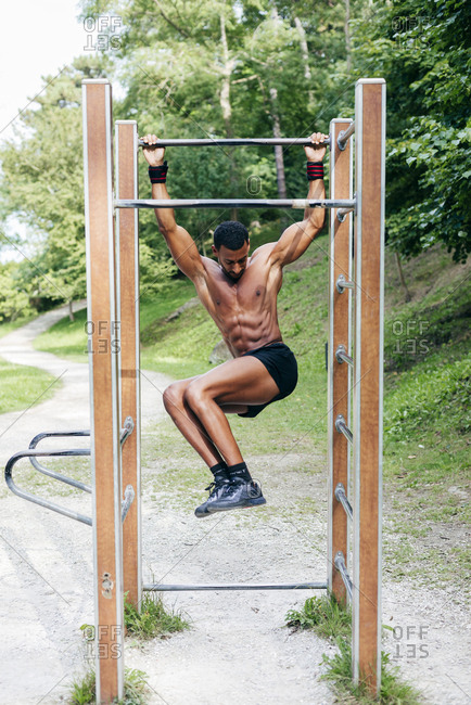 Shirtless muscular black man exercising and doing workout on bar in the park.