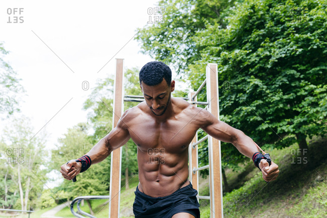 Shirtless successful African bodybuilder pulling rope and working out in park.