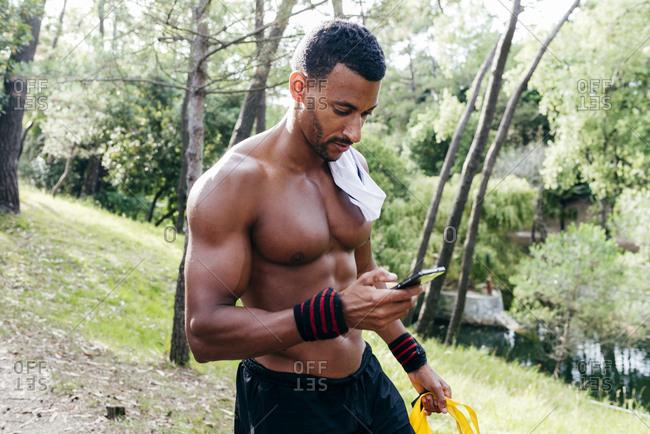 Shirtless bodybuilder man in park walking and browsing smartphone.