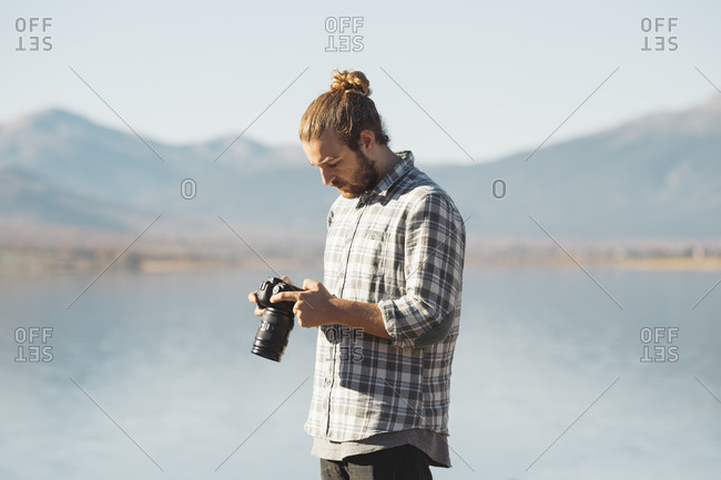 Side view of man photographer browsing camera standing at lake in hills.