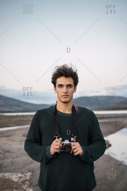 Young man photographer with camera standing in nature in hillside.