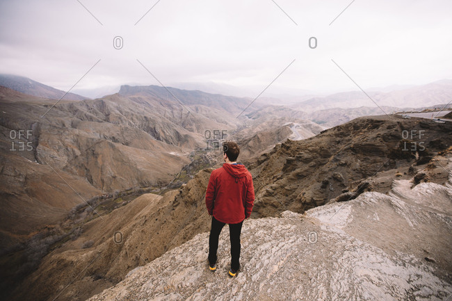 Male standing in mountains and looking into distance, back view.