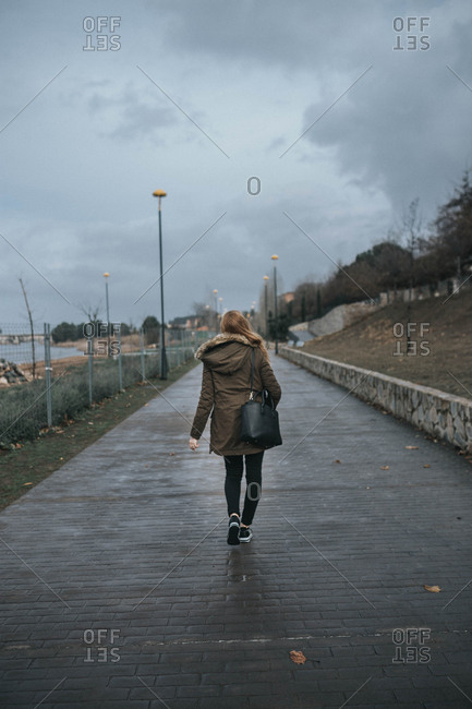 Young blond female on a walkway. Vertical outdoors shot.