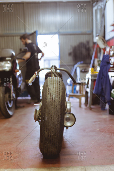 Classic custom motorcycle in repair shop. Vertical indoors shot.