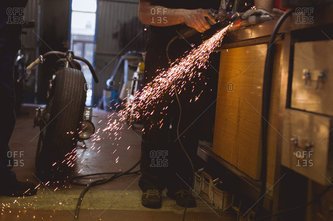 Horizontal indoors crop shot of worker cutting metal in workshop with bike parked near.