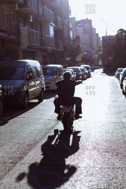 Back view of man riding a motorcycle in sunny day. Vertical outdoors shot.