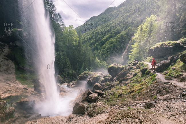 Tourist person standing in mountains with forest at waterfall.