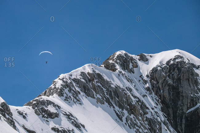 Unrecognizable tourist person gliding on parachute in snowy mountains.