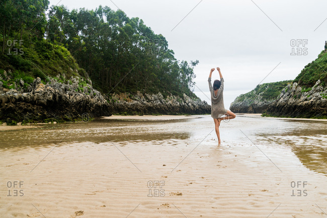 Back view of woman standing in yoga pose on one leg on sandy bay in ocean.