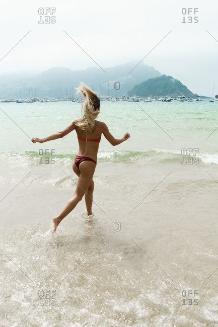 Happy woman running on tropical beach
