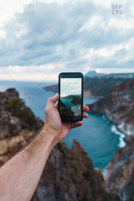 Crop male hand holding smartphone and taking shot of picturesque ocean view with cliffs.
