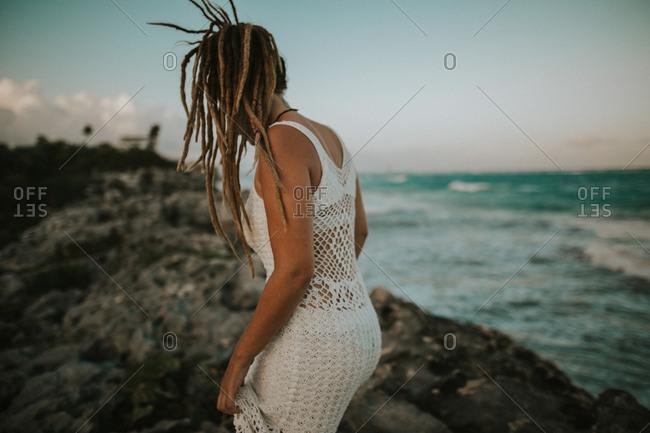Stylish woman walking on rocks