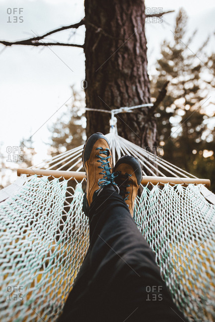 Crop shot of female feet relaxing in hammock among coniferous trees.