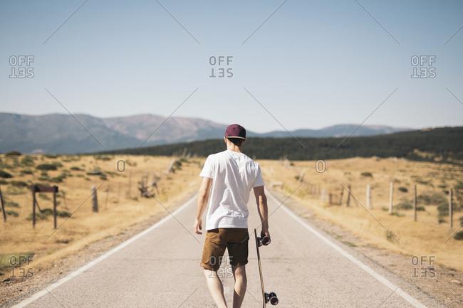 Back view of man with skateboard walking on rural asphalt road.