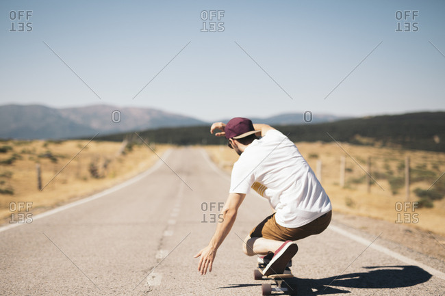 Man sitting and riding on skateboard
