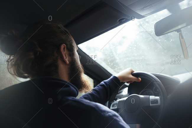 Unrecognizable bearded man driving car in sunny day.