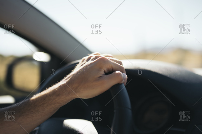 Hand of unrecognizable person on steering wheel while driving car in sunny day.