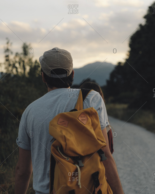 Back view of man with backpack standing on rural road in evening.