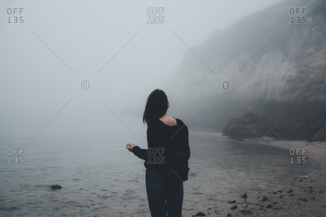 Back view of woman standing at the ocean near foggy mountains.