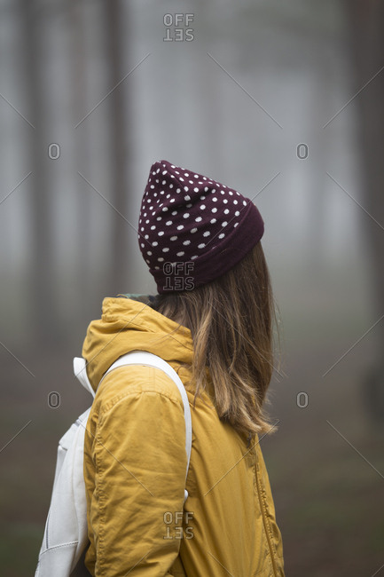 Side view of unrecognizable woman standing in misty dark forest.