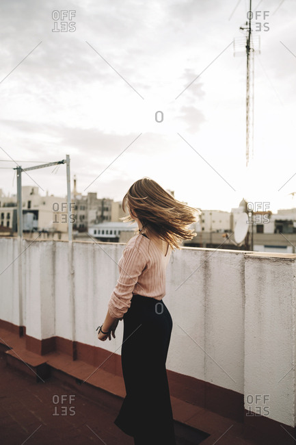 Back view of woman with flying hair standing on rooftop in town.