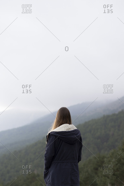 Woman standing in foggy forest