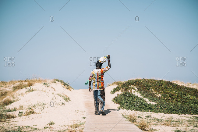 Back view of black man in colorful clothing walking on wooden walkway on shore taking off hat