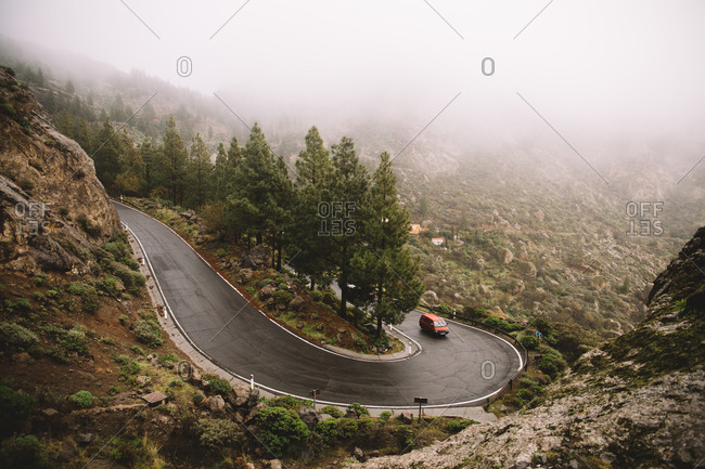 Car driving on a winding road in the mountains in the fog.