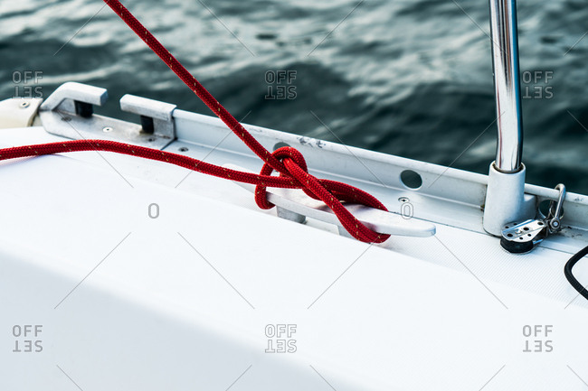 Close-up of red cord wrapped around rigging of yacht.