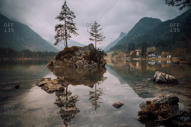 Lake surface with clear water and small rocky island with evergreen trees growing.