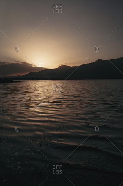 View to lake and coastal hills in the dusk in sunset lights.
