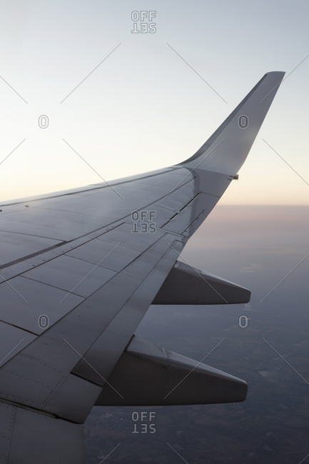 View to wing of airplane flying in cloudless evening sky.