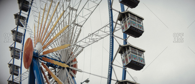 Crop huge spinning ferris wheel attraction in cloudy day.