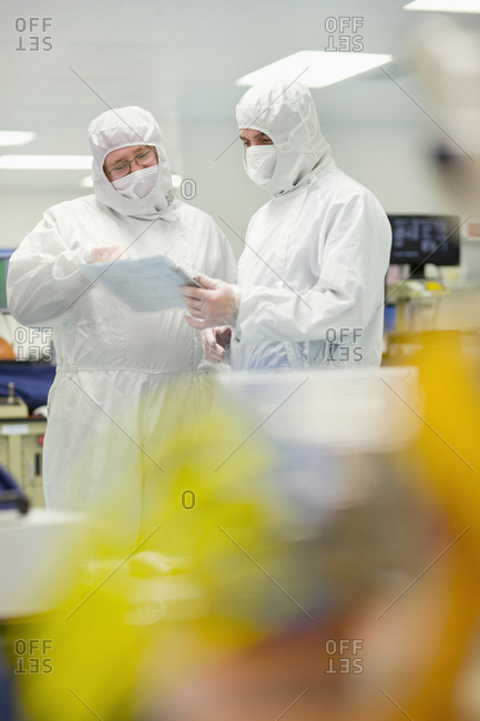 Scientists in clean suits discussing paperwork in silicon wafer manufacturing laboratory