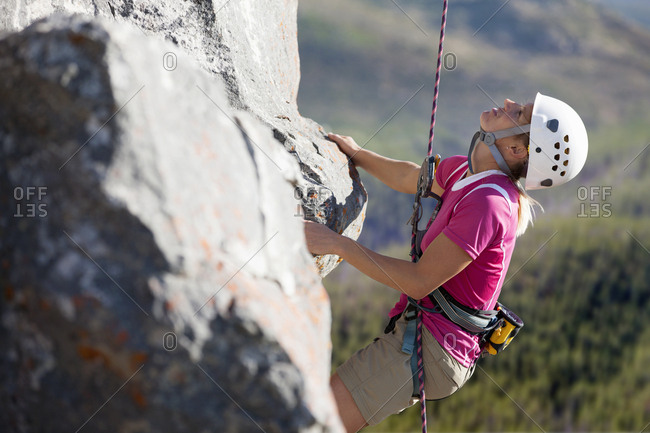 Female rock climber scaling rock face and looking up