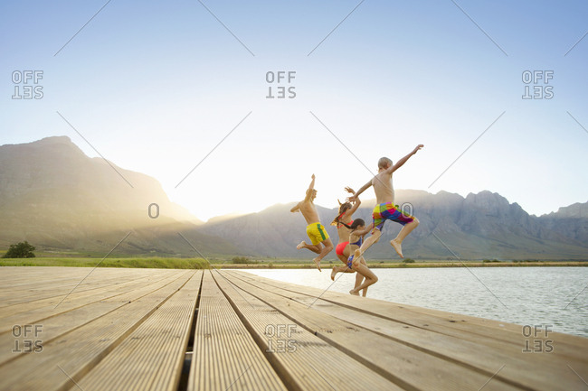 Family, in swimwear, jumping into a lake from a jetty