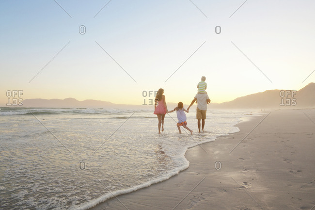 Happy family walking into distance, holding hands and son having piggy-back, on sunny beach