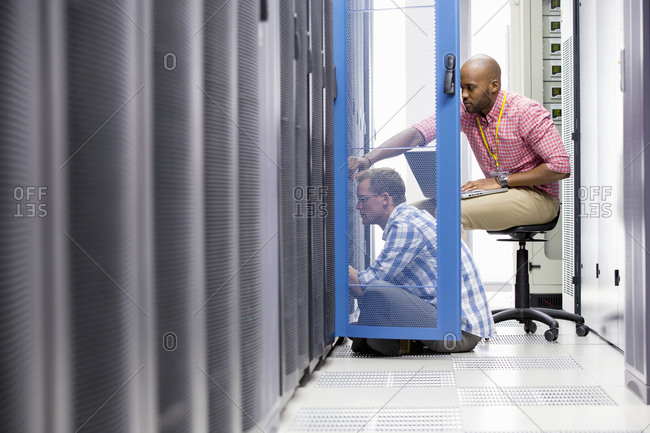 Technicians with laptop checking server in data center