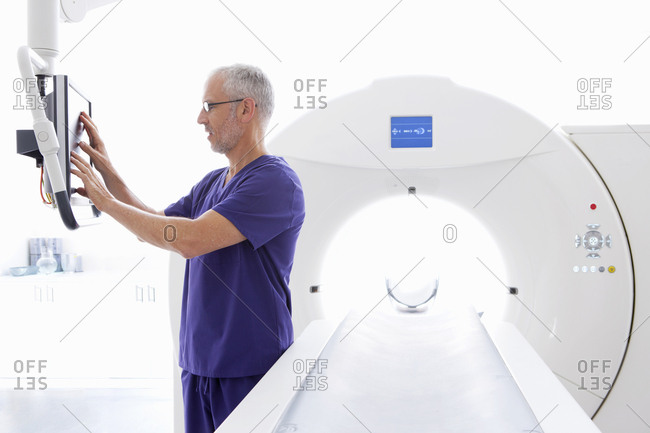 Doctor at computer monitor next to CT scanner in hospital
