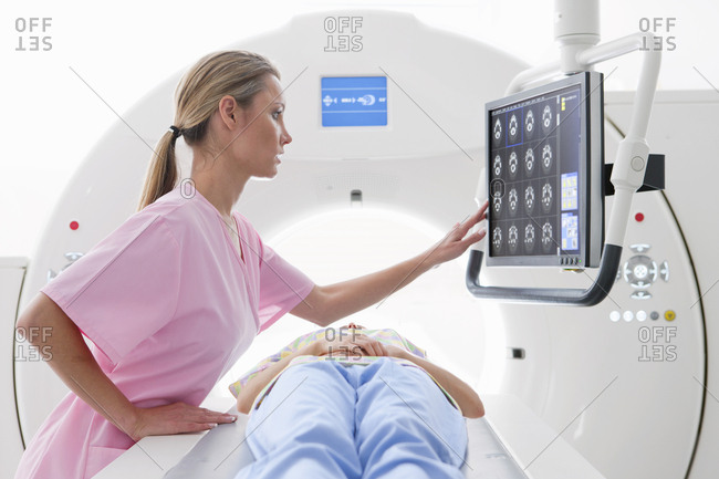 Nurse reviewing digital brain scan at CT scanner in hospital